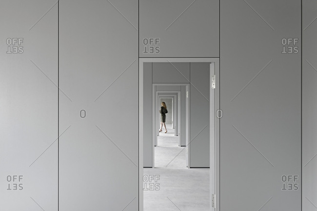 View through corridor of businesswoman walking in office
