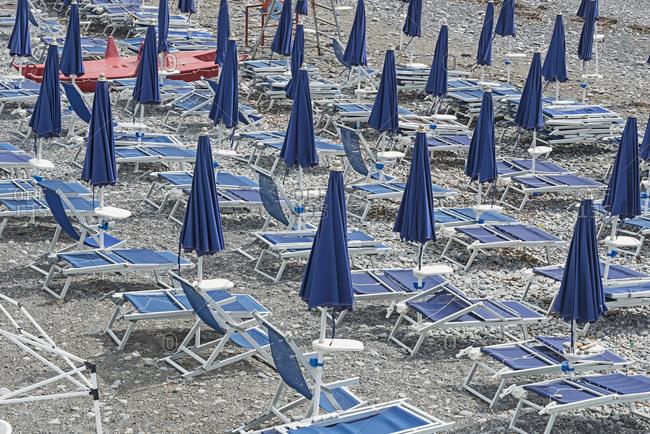 Closed blue parasols and lounge chairs on beach
