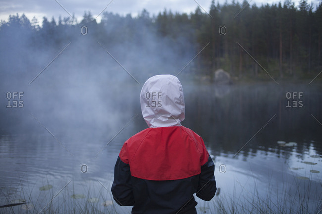 Rear view of child wearing raincoat at lake in foggy weather