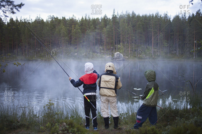 Rear view of children wearing raincoats fishing at lake in foggy weather