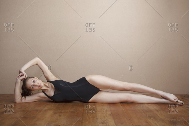 Portrait of beautiful woman wearing leotard while lying on hardwood floor against wall