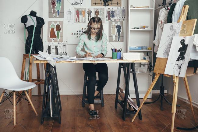 Beautiful female design professional working at workbench in studio