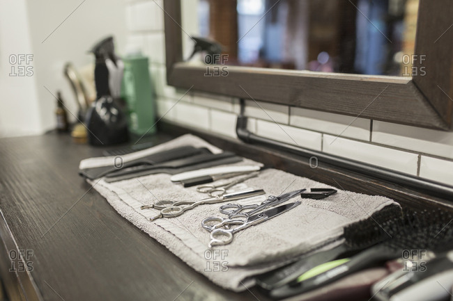 Close-up of various scissors and combs on napkin at hair salon