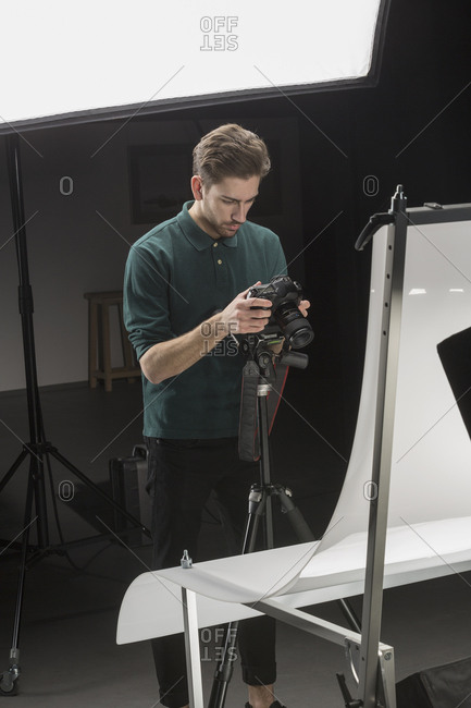 Confident photographer looking at backdrop while working in studio
