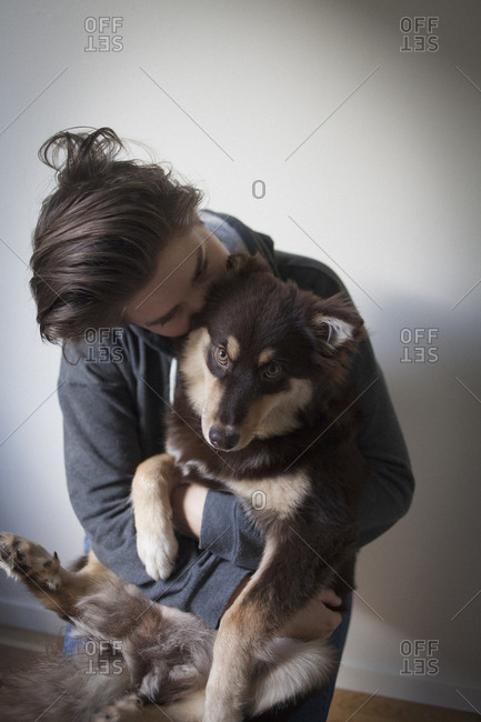 Affectionate young woman embracing dog against white background