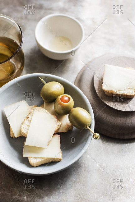 Mini toasts with semi-soft cheese and stuffed olives