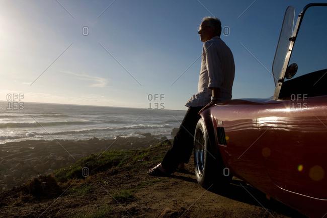 Older Man views sunset from car bonnet