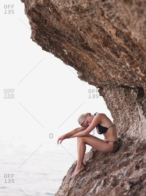 woman sitting on rocks at cliffs