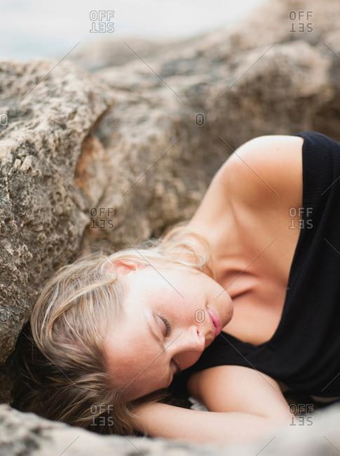 woman lying on rocks at cliffs