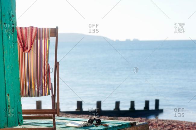 Empty deck chair by beach