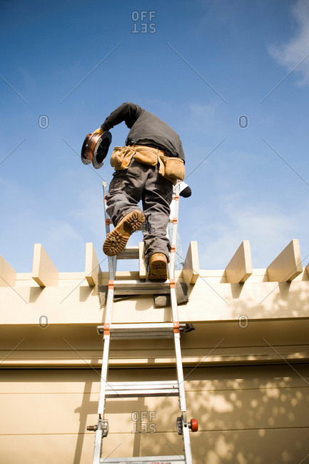 Workman on ladder to roof