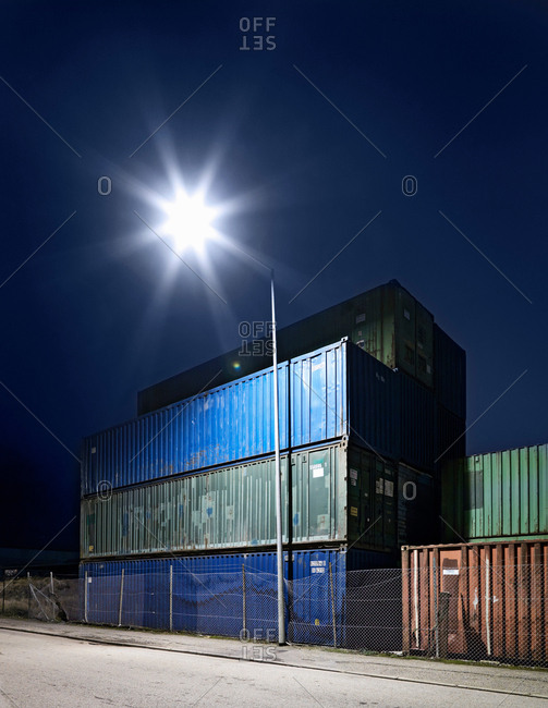 Lamppost by shipping containers at night