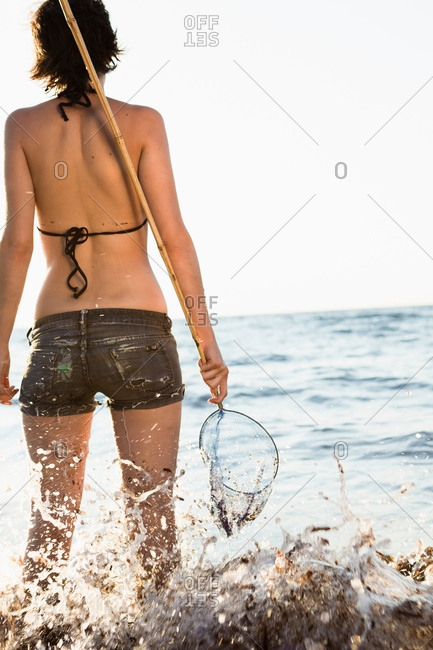 Woman playing with fishing net on beach