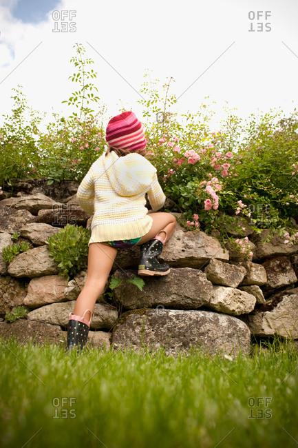 Girl climbing stone wall