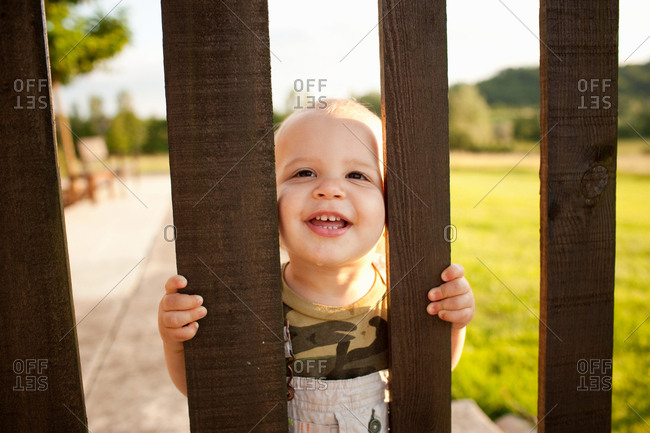 Toddler looking through wooden gate