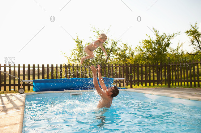 Father throwing son in air in swimming pool