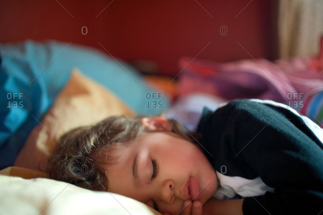 Young girl asleep on bed