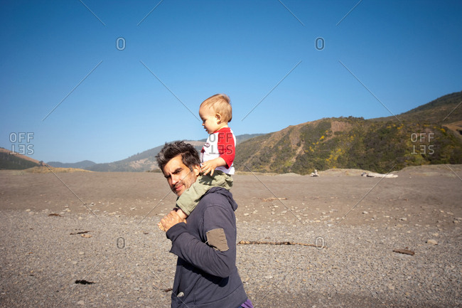 Father carrying son on shoulders in desert landscape