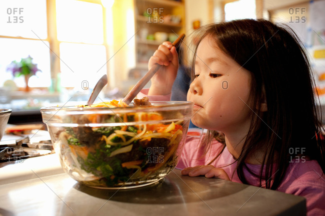 Girl mixing salad in salad bowl