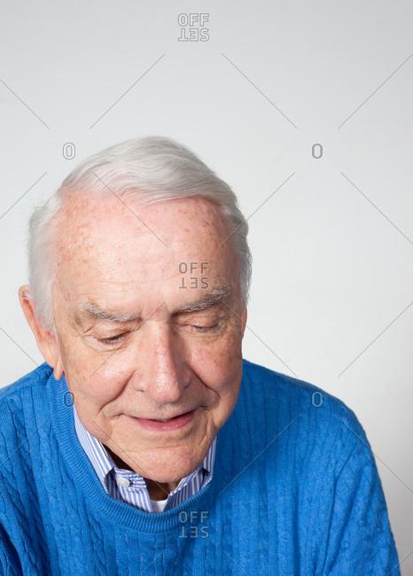 Senior man looking down, studio shot