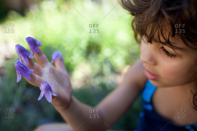 Young girl with flowers on fingers