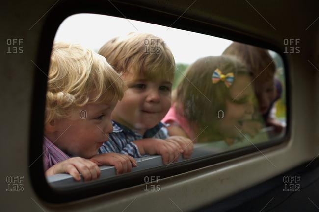 Four children peering through truck window