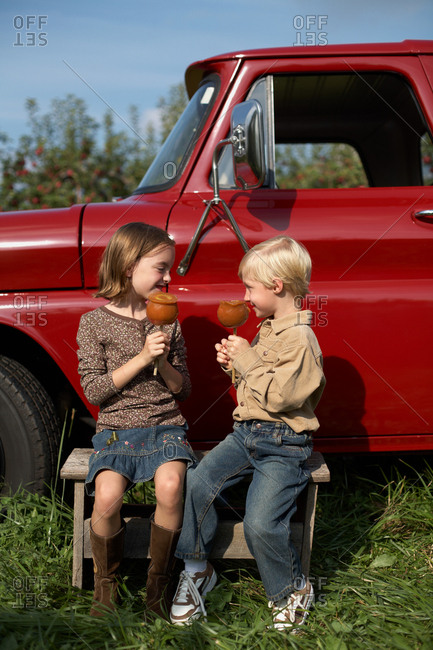 Boy and girl eating toffee apples by truck