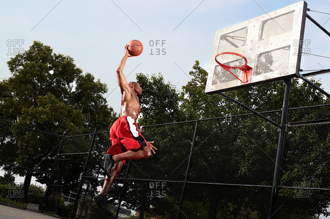 Young man leaping at basketball hoop
