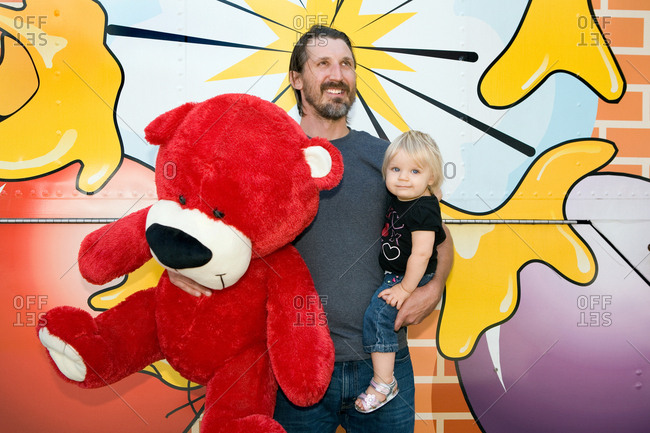 Man holding large teddy bear and son