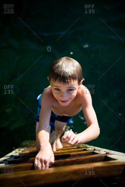 Boy climbing up ladder from the sea