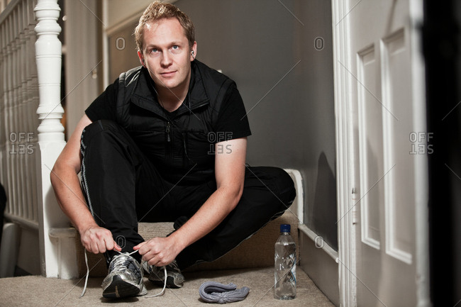 Mid adult man tying training shoe laces on steps