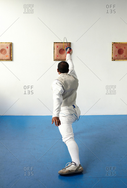 Male fencer holding foil to target, rear view