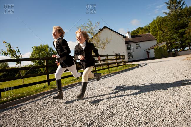 Boys running along gravel path of ranch