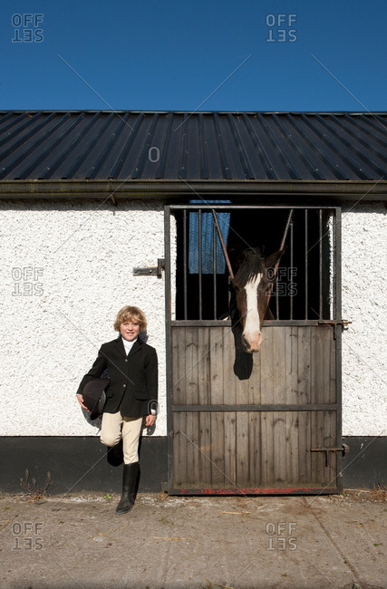 Boy standing by horse stables