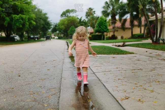 Little girl walking in rain puddles