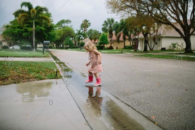 Little girl stomping in rain puddles