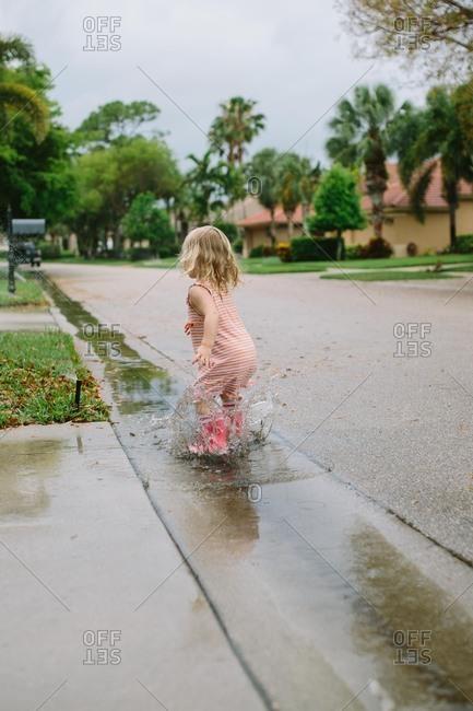 Toddler girl splashing in rain puddles