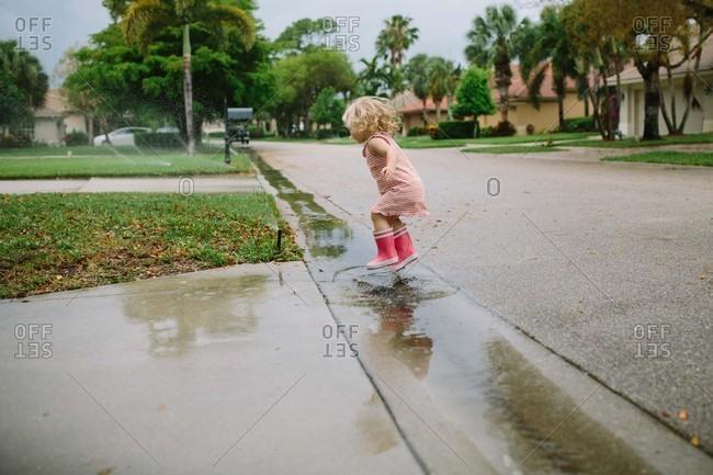 Toddler girl jumping in rain puddles