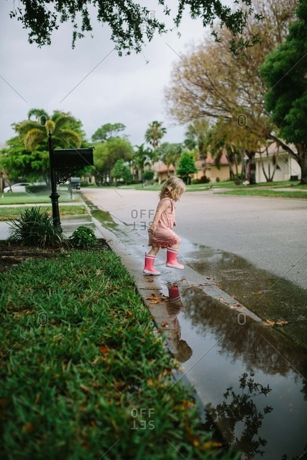 Toddler girl playing in puddles in the street