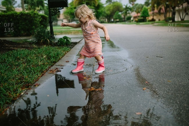 Little girl playing in puddles in the street