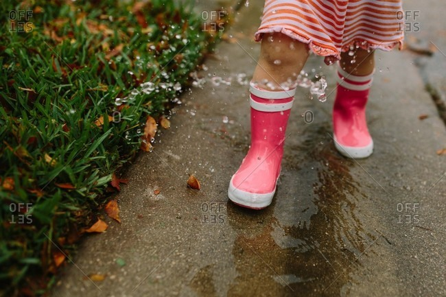 Close up of little girl splashing in puddles in the street