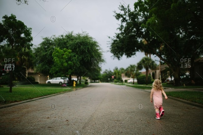 Toddler girl walking on street in residential neighborhood from behind