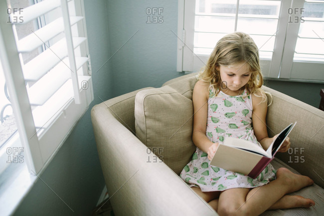 Young girl sitting on chair reading a book