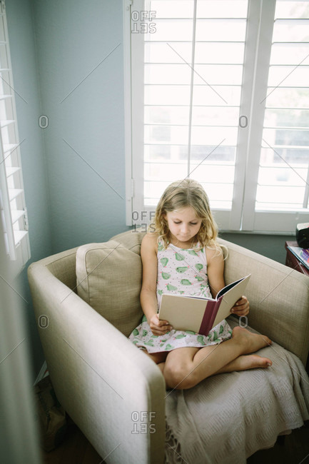 Little girl sitting on chair reading a book