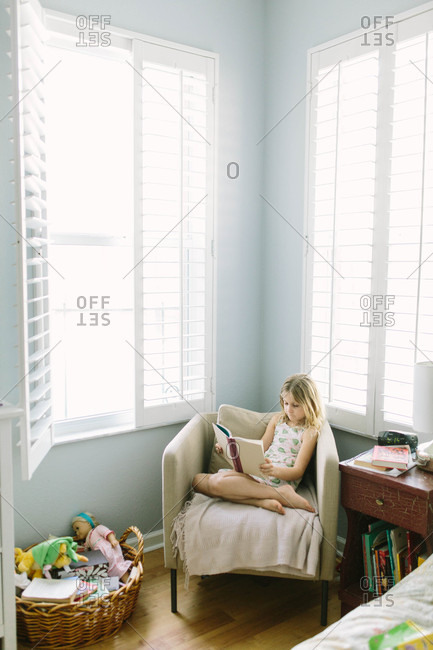 Young child sitting on chair reading a book