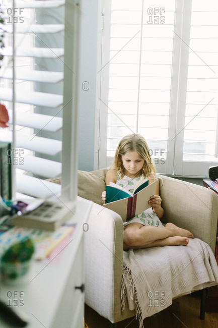 Blonde girl sitting on chair reading a book