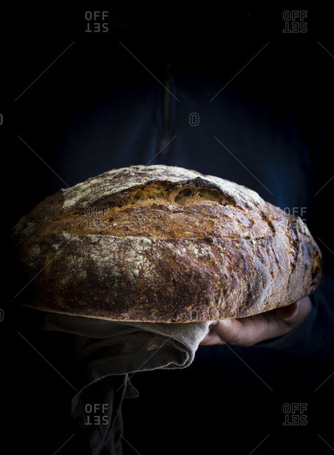 Man holding freshly baked sourdough bread front view