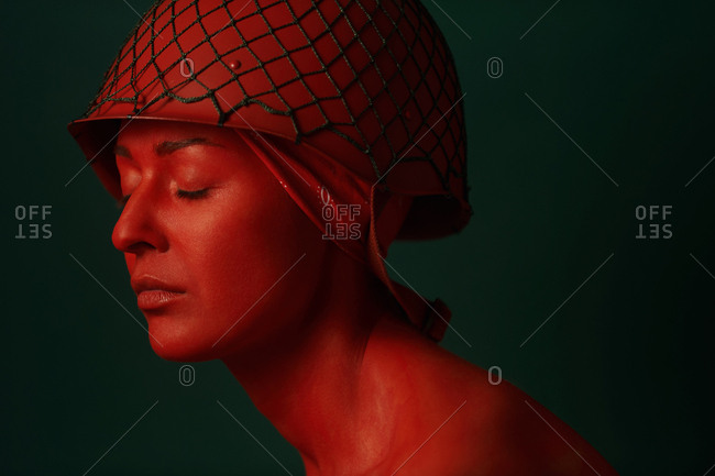 Close up  of female soldier with her face painted red against a dark green background