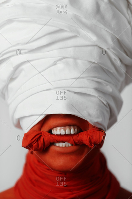 Close up of female with her face painted red wearing a white turban with a gag in her mouth
