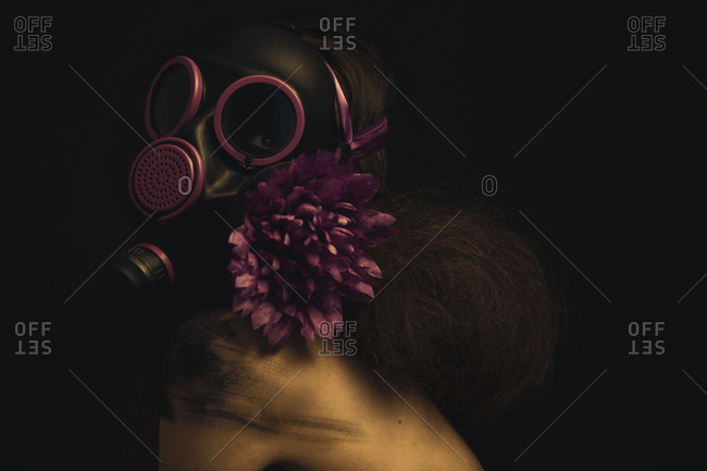 Close up of a woman with a retro hairstyle wearing a black gas mask and a purple flower in her hair